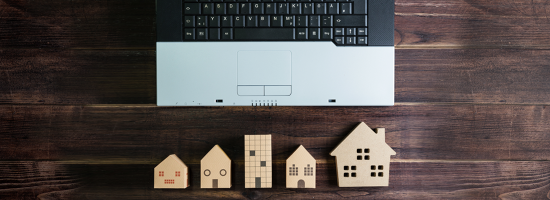 Wooden model houses by a laptop computer