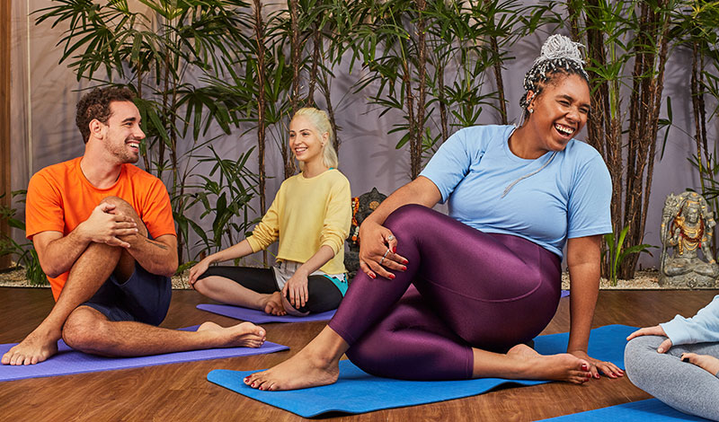 Two women and a man are stretching on yoga mats on the floor during a yoga session