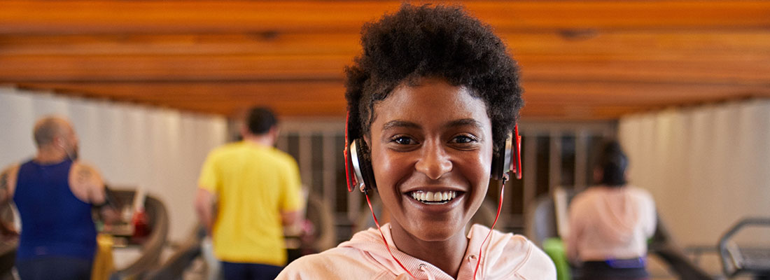 A young lady wearing headphones and smiling