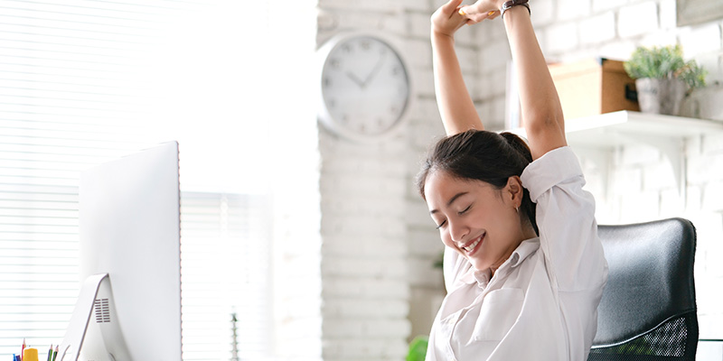 A young Asian woman is stretching high with her arms whilst sat at her desk
