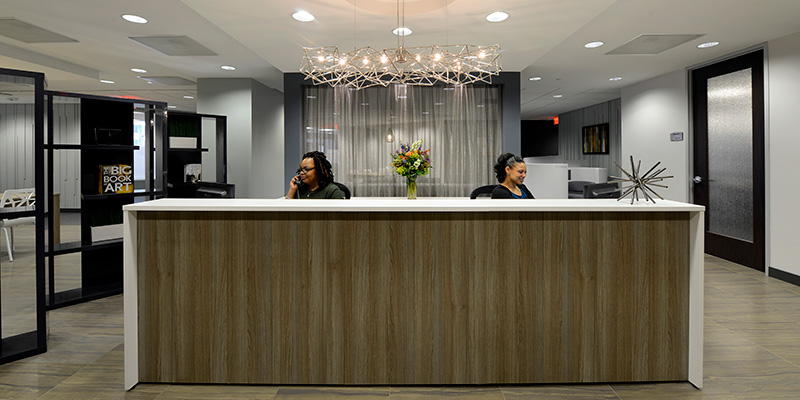 Two women are sat behind a Regus reception desk