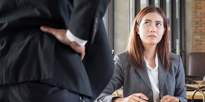 A businesswoman looking up from a desk at a man with his hand on his hip
